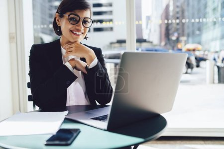 Portrait of cheerful businesswoman updating software on laptop doing remote job in cafe satisfied with prosperous career.Successful trader in stylish formal wear smiling at camera sitting at laptop
