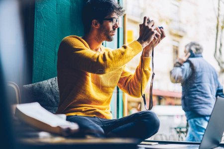 Male amateur photographer in eyeglasses focusing to make photos out of window sitting on windowsill.Young bearded man resting in coworking space and taking pictures for portfolio on vintage camera
