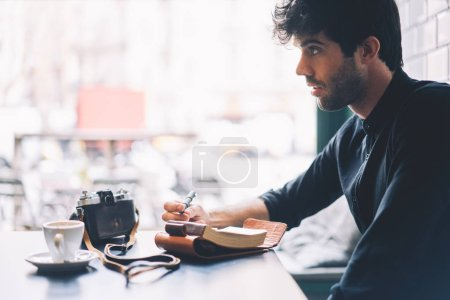 Side view of male amateur dressed in trendy black shirt writing down text information in notepad sitting at coffee table with vintage camera in stylish cafeteria interior.Copy space area