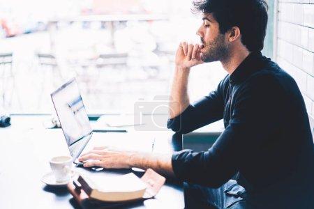 Diseñador gráfico hombre pensativo viendo webinar en dispositivo portátil moderno sentado en la cafetería. Estudiante masculino de sitios web en internet vía conexión a internet en netbook digital dispositivo de navegación