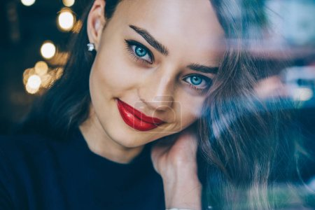 Cropped portrait of beautiful female 20 years old with amazing blue eyes and red lips.Close up image of gorgeous Ukrainian women with perfect skin and charming smile on face looking at camera