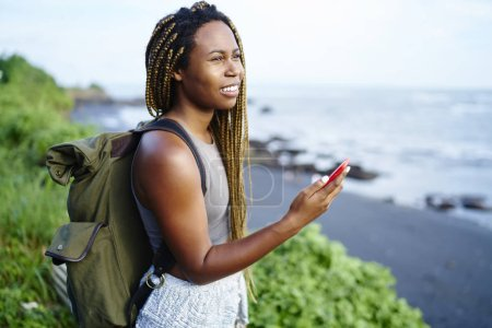 Cheerful attractive tourist with dark skin enjoying tropical scenery of seashore holding smartphone in hands.Afro american young woman with travel backpack admiring landscape of island during trip