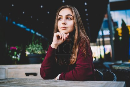 Pensive attractive caucasian girl in casual wear resting on cafe terrace dreaming about weekends, thoughtful teen cute female hipster sitting at table looking away planning day during weekends