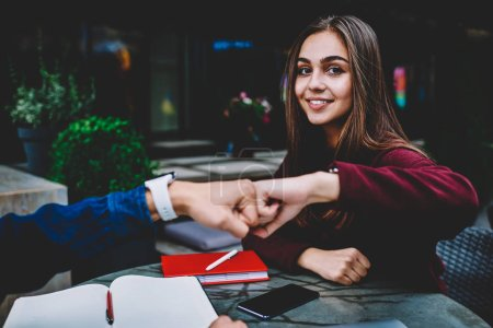 Portrait of charming young female student greeting with male colleague bumping fist sitting on rettace, cute hipster girl looking at camera while knuckles with guy satisfied with agreement of project