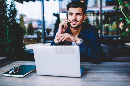 Photo for Skilled pensive young businessman listening information while having mobile consultancy with operator,male freelancer doing remote job sitting with laptop in cafe and talking on phone about project - Royalty Free Image