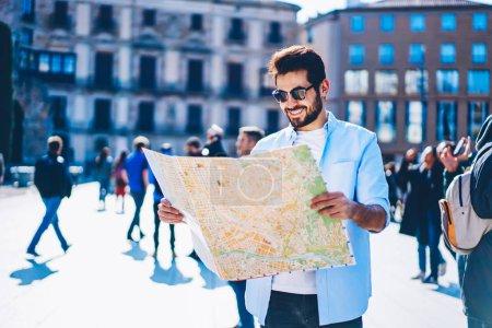 Happy barbu occasionnels touristiques habillé dans des lunettes de soleil élégantes bénéficiant de voyage d'aventure et lire l'homme pour effectuer une recherche permanente de destination centre-ville architectural en journée ensoleillée durant les vacances d'été