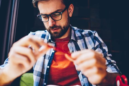 Pensive bearded young man in optical eyeglasses for vision correction studying in coworking space.Concentrated hipster guy dressed in casual stylish shirt sitting in coffee shop interior