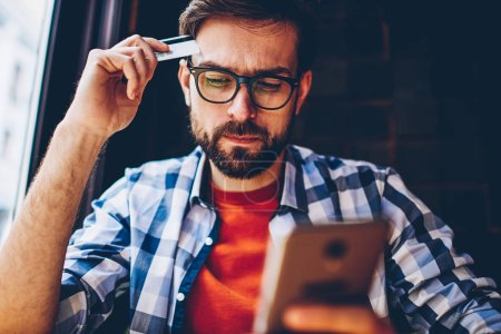 Pensive bearded young man in optical eyeglasses for vision correction holding banking card in hands while making payment online on website using free internet connection on smartphone device