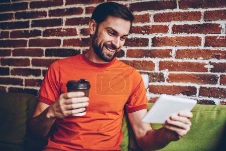 Cheerful bearded young man holding coffee to go in hands and watching funny videos in social networks on touch pad via 4G internet.Positive male blogger communicating via video call on tablet device