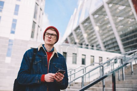 Photo for Thoughtful hipster student in eyewear walking on street with smartphone in hands to send sms message.Pondering young man checking mail with notifications in social networks on mobile phone - Royalty Free Image