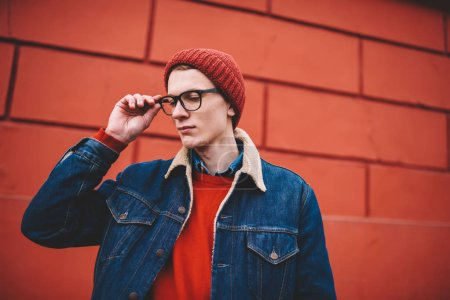 Young man in stylish red hat and optical eyeglasses for vision correction looking down.Casual dressed hipster guy in denim jacket standing in urban setting on promotional background
