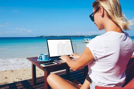Photo pour Jeune femme millénariste keyboarding sur netbook avec écran maquette communiquer dans le chat en ligne assis près de l'océan, femme d'affaires travaillant à distance en vacances dans un environnement tropical profiter de la natur - image libre de droit