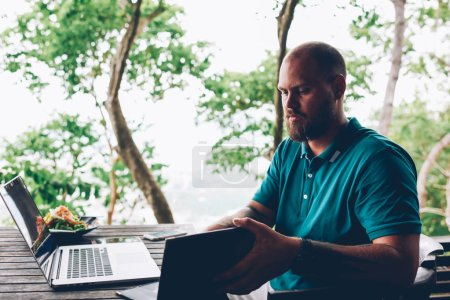 Photo for Serious caucasian man open menu looking for meals on lunch sitting with laptop for remote job in asian cafe terrace, pensive male blogger checking bill for salad using wifi connection for remote job - Royalty Free Image