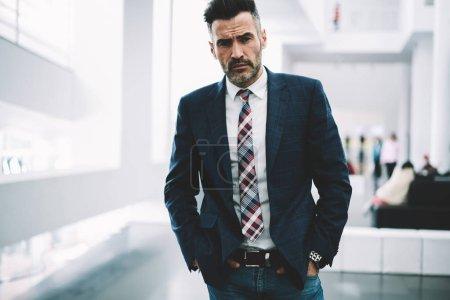 Photo pour Portrait demi-longueur d'homme d'affaires confiant avec succès habillé en tenue formelle debout dans le bureau.Sérieux mature fier PDG en suit.Prosperous entrepreneur d'âge moyen regardant la caméra - image libre de droit