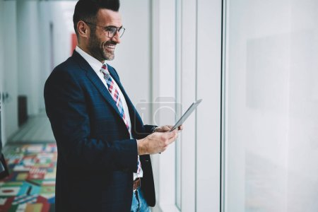 Cheerful prosperous businessman 50 years old dressed in formal wear holding digital tablet to check mail while looking out of window.Positive mature proud ceo laughing during money transaction