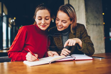 Successful two hipster girls drawing design sketch for new project teamworking in coffee shop.Cheerful friends writing down common plans of collaboration in notepad resting together in coworking