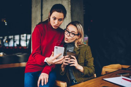 Excited hipster girls surprised with cool design collection during watching online video on smartphone connected to free internet. Wondered young women reading shocked news on website on cellular