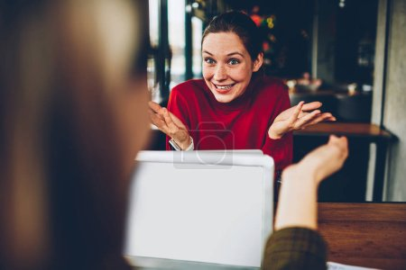 Cheerful young student explaining new successful plan colleague during distance job at laptop device connected to wireless 4G internet.Positive hipster girl telling funny story while gesturing hands