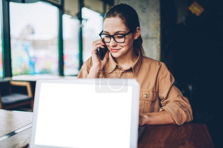 Photo for Brunette female manager in eyeglasses calling on smartphone.Freelancer in eyewear talking with operator on telephone about mobile benefits during remotely work at laptop computer with blank screen - Royalty Free Image