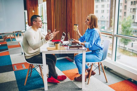 Cheerful male and female colleagues having fun joking during coffee break in office communicating,happy coworkers discussing ideas for creative designer project cooperating in friendly atmosphere