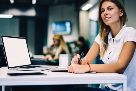Young female blogger thinking about creative idea for publication editing article in netbook,clever woman pondering on homework task looking away sitting near laptop computer with mock up screen