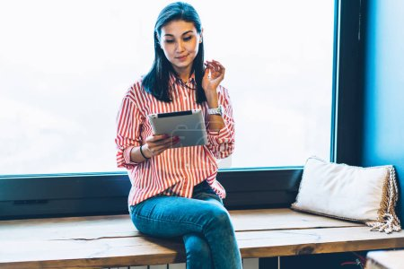 Young gorgeous brunette blogger make publication in personal website using modern touch pad and wireless connection.Cute hipster girl reading news in social networks on digital tablet sitting indoors