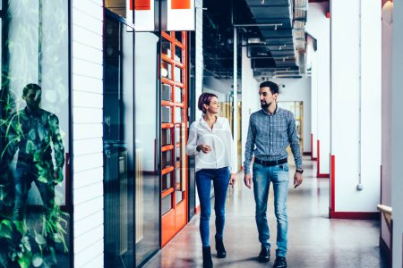 Photo for Young good looking positive male and female employees partners communicating with each other while going through office.Happy hipster guys discussing business project ideas during standing indoors - Royalty Free Image