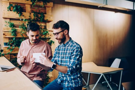 Photo pour Jeunes hipsters vérification nouveau pc portable et apps communiquant dans coworking espace pause, métier qu'il les développeurs satisfait mise à jour logiciel sur tablette numérique discuter des idées pour technolog - image libre de droit