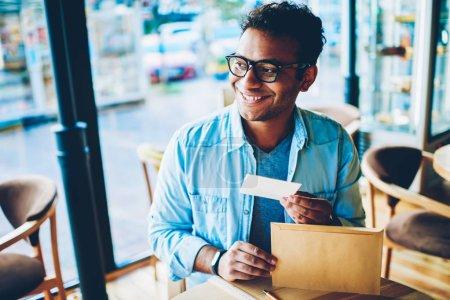 Photo pour Image rapprochée d'un bel entrepreneur hindou souriant tenant une petite lettre du colis brun clair et excité par le contenu.Mature beau homme heureux dans des lunettes fraîches assis dans un café - image libre de droit