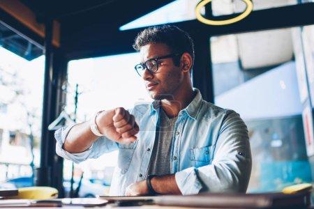 Photo pour Mature beau réfléchissant entrepreneur masculin vérifier le temps sur smartwatch en attendant la réunion avec le client dans le café shop.Good homme planification horaire de travail en utilisant un appareil numérique à l'intérieur - image libre de droit