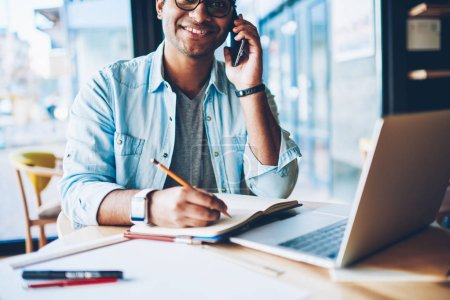 Photo for Half length portrait of smiling professional freelancer having mobile conversation with client on telephone connected to 4G.Happy male person talking with friends and recording information to notepad - Royalty Free Image