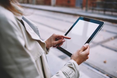 Photo for Cropped view of young woman's hands touching mock up display of modern tablet device with 4G internet.Hipster girl choosing app for download on touch pad with blank screen area for website content - Royalty Free Image