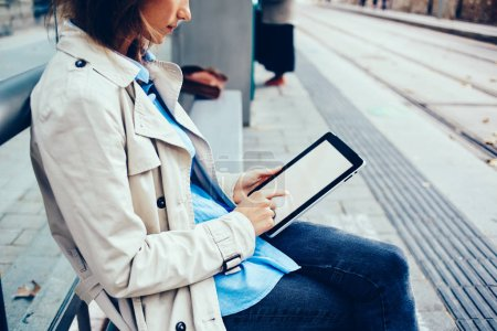 Photo for Cropped side view of stylish young woman choosing media files on modern tablet via 4G internet connection sitting on tram stop.Caucasian female typing text on blank screen of digital touch pad - Royalty Free Image