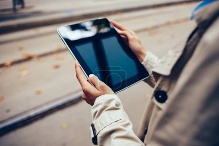 Photo for Cropped view of young woman's hands holding modern touch pad device connected to 4G internet.Updating profile in social networks on digital tablet with black screen area.Hipster girl with gadget - Royalty Free Image