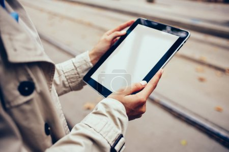 Photo for Cropped view of hipster girl holding digital tablet with blank screen area for your internet website.Installing application on modern touch pad device with copy space in woman's hands - Royalty Free Image
