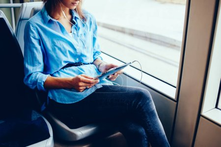 Photo for Cropped view of hipster blogger in earphones watching tutorial online on modern touch pad device connected to transport public free wifi sitting in tram.Young woman listening music on tablet - Royalty Free Image