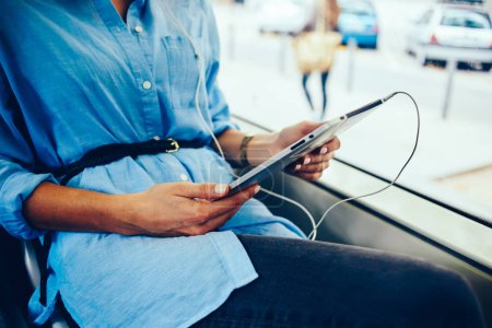 Photo for Cropped view of woman's hands holding modern tablet with earphones sitting in tram.Hipster girl listening audio music downloaded in player on touch pad using public wireless internet connection - Royalty Free Image