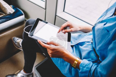 Photo for Cropped view of young woman choosing audio song in playlist downloaded on modern touch pad with earphones.Female person touching with finger on blank screen area of digital tablet using transport wifi - Royalty Free Image