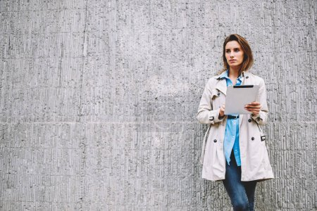Photo for Contemplative caucasian young woman looking away while chatting online in social networks on digital tablet with 4G internet connection standing on promotiobal background with copy space area - Royalty Free Image