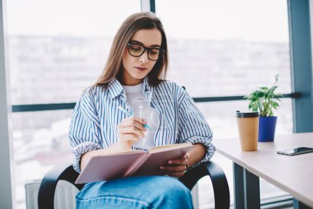 Photo for Clever female employee in eyewear writing in notepad concentrated on working process in office, serious caucasian smart woman making notes of ideas for article sitting at comfortable working plac - Royalty Free Image