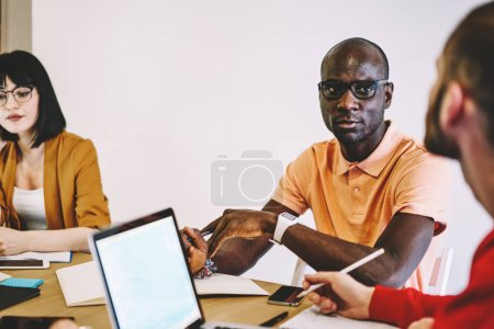 Photo for Multicultural young people in smart casual wear discussing working plan of collaboration on design project sitting at meeting table in office.Diverse team of employees cooperating on solution - Royalty Free Image