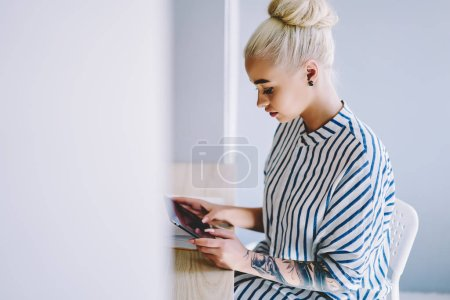 Pensive hipster girl making payment online on website using wireless internet on modern tablet.Blonde young woman installing app and chatting in social networks on digital touch pad device