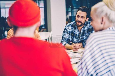 Photo pour Jeune homme positif vêtu de vêtements décontractés intelligents riant tout en discutant d'idées créatives et de stratégies productives avec des collègues ayant une réunion de remue-méninges assis à table dans un bureau moderne - image libre de droit