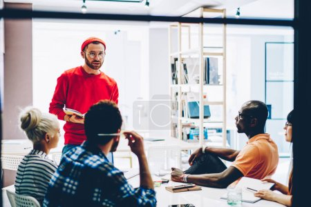 Photo for Creative male teacher with notepad in hands talking with multicultural students about business strategy during lesson in college.Young man coach explaining business strategy to group of employees - Royalty Free Image