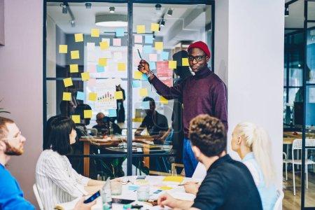 Photo pour Chic décontracté, habillée sombre peau jeune homme tenue de cours d'apprentissage de langue pour groupe de jeunes gens et pointant sur autocollants colorés avec des mots étrangers, collés sur un mur de verre en coworking élégant - image libre de droit