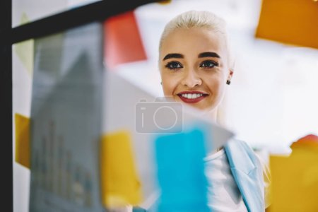 Happy young woman dressed in smart casual wear looking at colorful stickers with foreign words during lesson.Positive blonde hipster girl smiling while standing behind glass wall in modern office