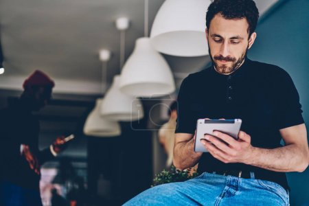 Caucasian bearded young man typing on digital tablet in search media files during working process in modern office.Pensive hipster guy updating profile on touch pad using wireless 4G internet