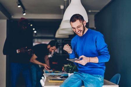 Overjoyed caucasian young man happy with victory of own project while reading results on internet website on touch pad.Positive hipster guy celebrating win while watching live stream on tablet