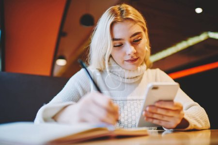 Young woman making notes using organizing application on cellular for planning tasks and learning process, female writing in notepad information from web page browsed on smartphone in cafe interior
