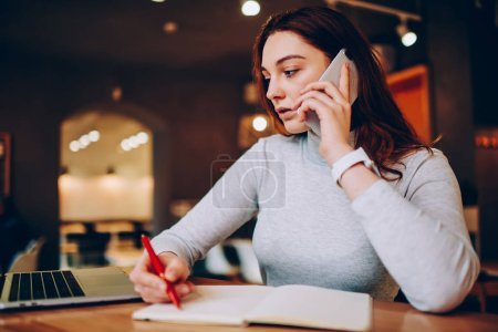 Professional female freelancer making telephone call planning working process in notepad, young woman writing information during mobile phone consultation with service operator sitting at caf
